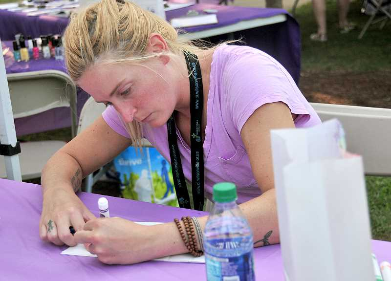 Erica Behler of Wilsonvile decorates a luminaria in memory of her grandfather.