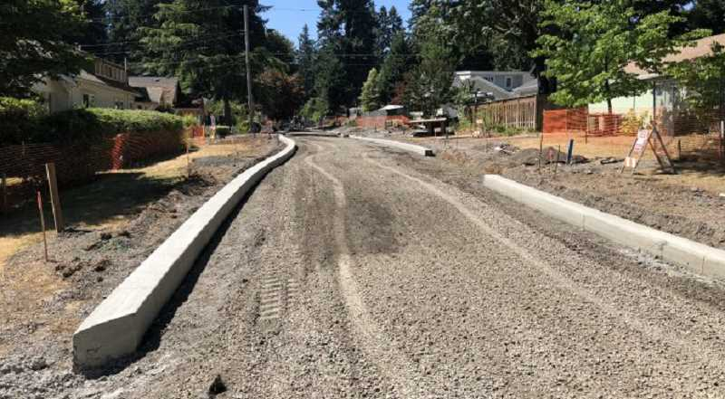 PHOTO COURTESY OF CITY OF LAKE OSWEGO - Crews have poured the concrete that will form the new edges of D Avenue for enhanced drainage. The first layer of central asphalt is scheduled to be poured Aug. 23-24.