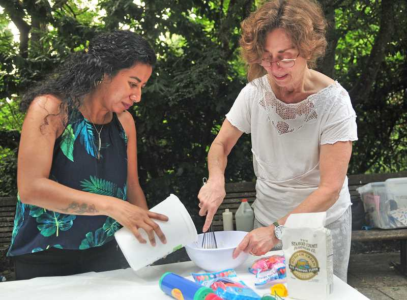 Patti Zavala, left, and Tamara Gilbert mix up another batch of paste for making the pinatas.