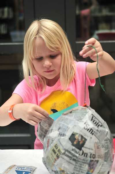 VERN UYETAKE - Sabine Howell, 7, of West Linn, concentrates as she adds more layers of paper to her pinata.