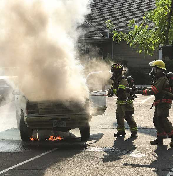JASON CHANEY - Crook County Fire and Rescue personnel try to put out a fire under the hood of a Ford Explorer after responding police spent two fire extinguishers trying to put it out.