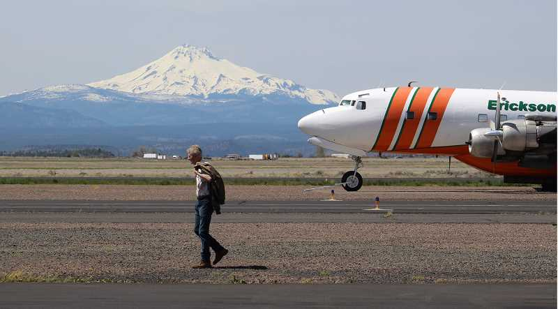 HOLLY M. GILL/MADRAS PIONEER - Jack Erickson strolls across the runway area at Madras Municipal Airport, with Mount Jefferson and one of Erickson Aero Tanker's seven MD-87 firefighting tankers in the background.