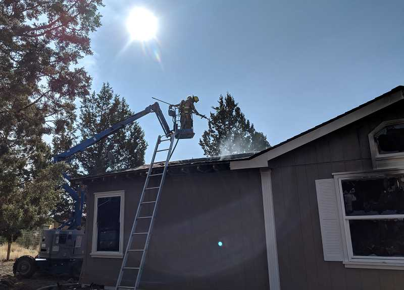 SUBMITTED PHOTO - A Crooked River Ranch Fire and Rescue firefighter on a man lift works to extinguish a fire in a manufactured home on Aug. 13. The roof had collapsed, making it dangerous to enter the home.