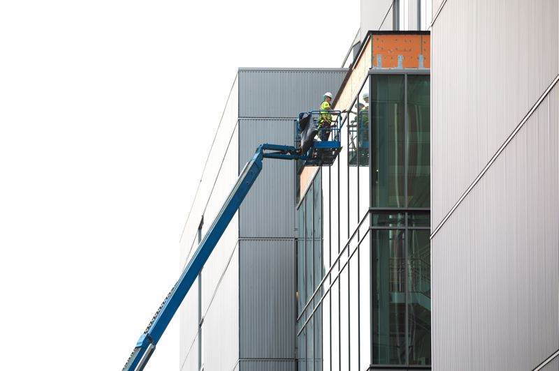 PORTLAND TRIBUNE: JONATHAN HOUSE - A construction worker puts the finishing touches on the Knight Cancer Institute's sawtooth-style windows on the south side. Top scientists gave up the best views so that other workers could enjoy them.