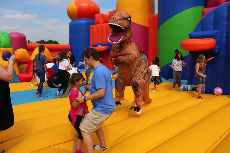 STAFF PHOTO: OLIVIA SINGER - To add to the inflatable fun, one local participant arrived in their dinosaur suit, bouncing with the crowd.