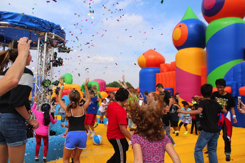 STAFF PHOTO: OLIVIA SINGER - Kids danced and reached in the air as the confetti fell over them in the middle of Saturday's bounce session.