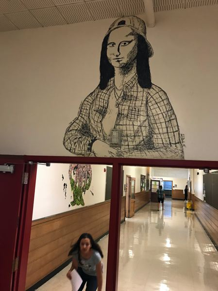 TIMES PHOTO: DANA HAYNES - A student dashes to class under the drawing of Mona Lisa as a Northwesterner. The mural likely will be lost when the school is demolished.