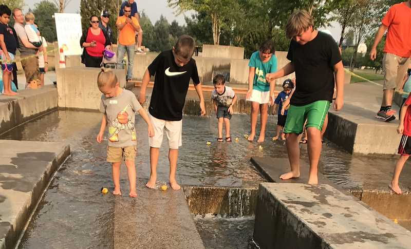 SPOKESMAN PHOTO: LESLIE PUGMIRE HOLE - Youngsters try their hand at rubber ducky captainship during a race down the fountain at Towns Center Park.