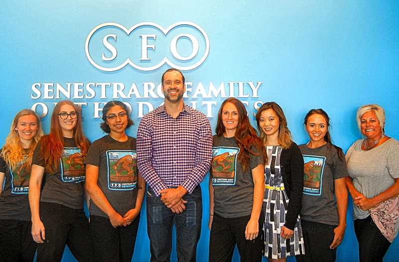 ELIZABETH USSHER GROFF - Dr. Seth Senestraro stands with his team at Senestraro Family Orthodontics at his new Woodstock Boulevard office. Dr. Seth also has fourteen year-old twin boys – not pictured – who occasionally help around the office.