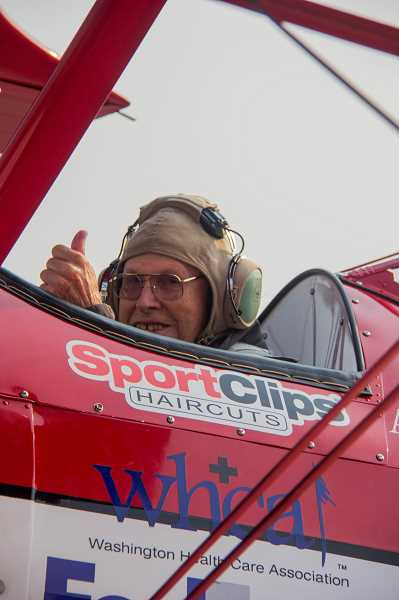 A veteran gives a thumbs up as he prepares to be taken up in a Boeing Stearman biplane at Aurora State Airport.