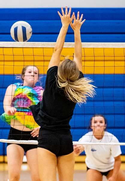 LON AUSTIN/CENTRAL OREGONIAN - Raegan Wilkins goes up for a kill during a team volleyball camp earlier this summer, while Mekynzie Wells covers. Wilkins led the Cowgirls in hitting on Thursday as they went undefeated at the Hood River jamboree.