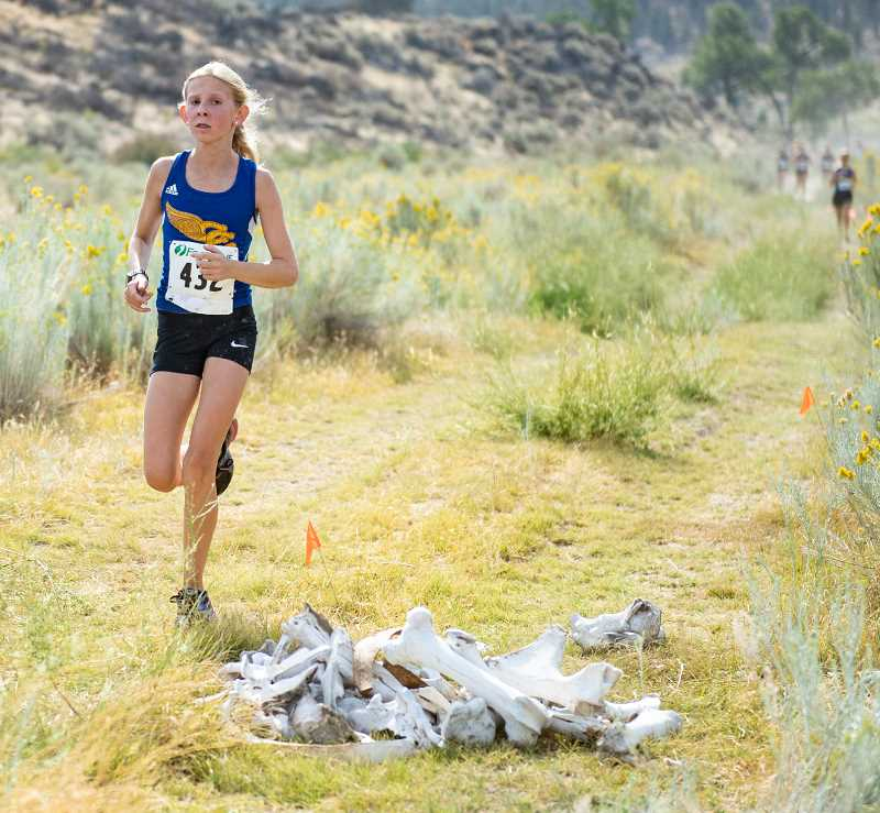 LON AUSTIN/CENTRAL OREGONIAN - McCall Woodward runs around a pile of water buffalo bones with just over a mile to go in Saturday's Jere Breese Memorial Ranch Stampede. Woodward, a freshman, had a sizeable lead on the runners behind her and finished 24th overall in the race with a time of 27:09.