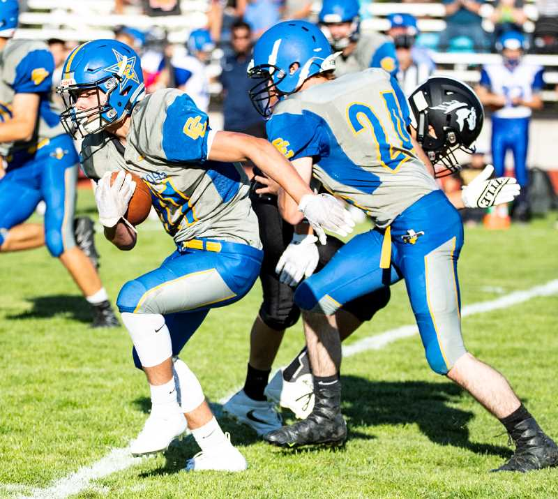 LON AUSTIN/CENTRAL OREGONIAN - Jacob Kleffner returns an interception against Sisters, while E.J. Allen blocks.