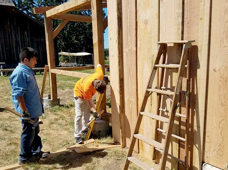 SUBMITTED PHOTO - Youths from Anvil Academy apply exterior boards to a replica blacksmith shop erected on land adjacent to the visitor's center at the state park.
