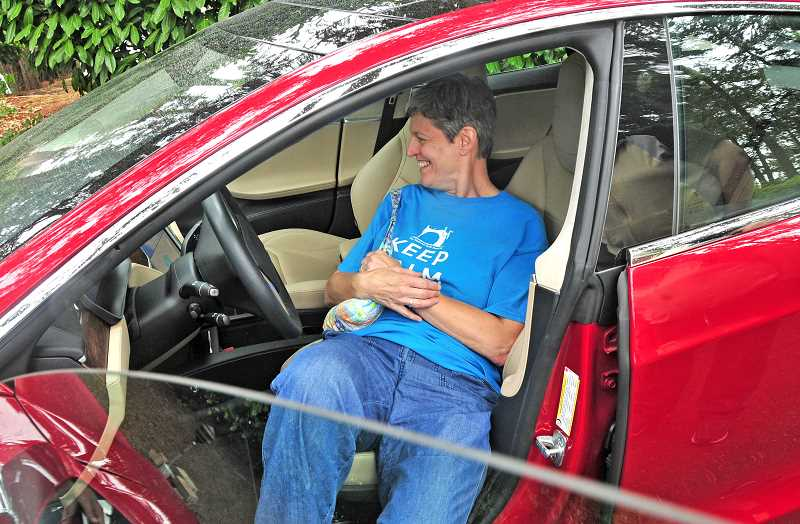 REVIEW PHOTO: VERN UYETAKE - Claudia Jakim checks out the driver's seat of the Tesla Model S at Sunday's Electric Vehicle Fair at the Oswego Heritage House.