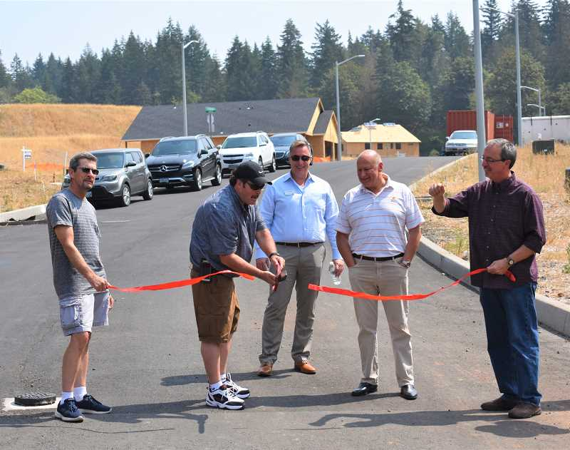ESTACADA NEWS PHOTO: EMILY LINDSTRAND - Estacada Mayor Sean Drinkwine (center) cuts the ribbon for the newest phase of the Cascadia Ridge subdivision on Tuesday, Aug. 21.