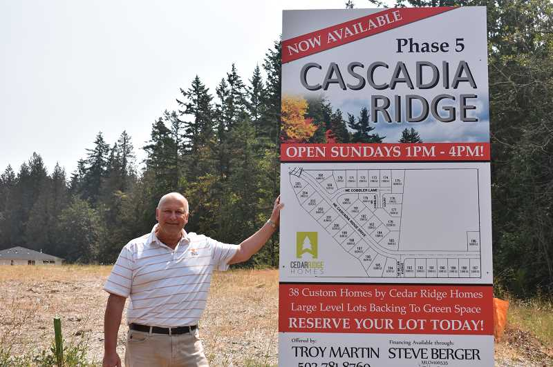 ESTACADA NEWS PHOTO: EMILY LINDSTRAND - Troy Martin, realtor for the Cascadia Ridge subdivision, stands next to a sign that details the community's next phase.