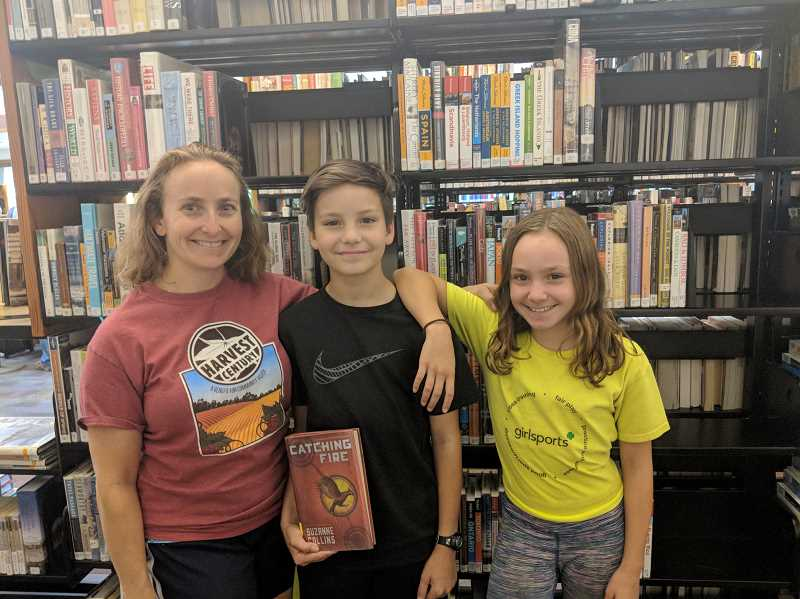 ESTACADA NEWS PHOTO: EMILY LINDSTRAND - Laura, Sam and Sophia Montez, pictured here at the Estacada Public Library, enjoyed reading a variety of books this summer.