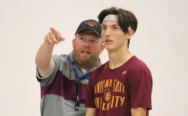PAMPLN MEDIA: JIM BESEDA - Milwaukie coach Colin Schaeffer (left) talks strategy with junior quarterback Nick Cooper during Wednesday's practice at the Oregon Premier Futsal indoor practice facility in Clackamas.