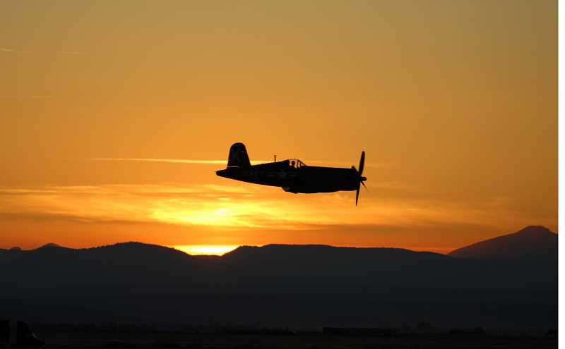 HOLLY M. GILL/MADRAS PIONEER - A U.S. Navy fighter, the F4U-7 Corsair, makes a quick pass at sunset Friday night. The aircraft is part of the Erickson Aircraft Collection.