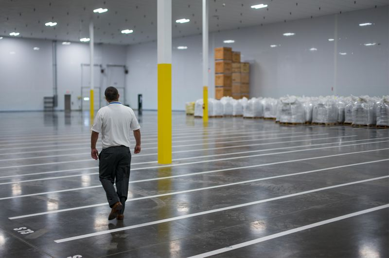 PAMPLIN MEDIA GROUP: KIT MACAVOY - Jason Costa, the plant's operations manager, walks through a predominately empty section of the