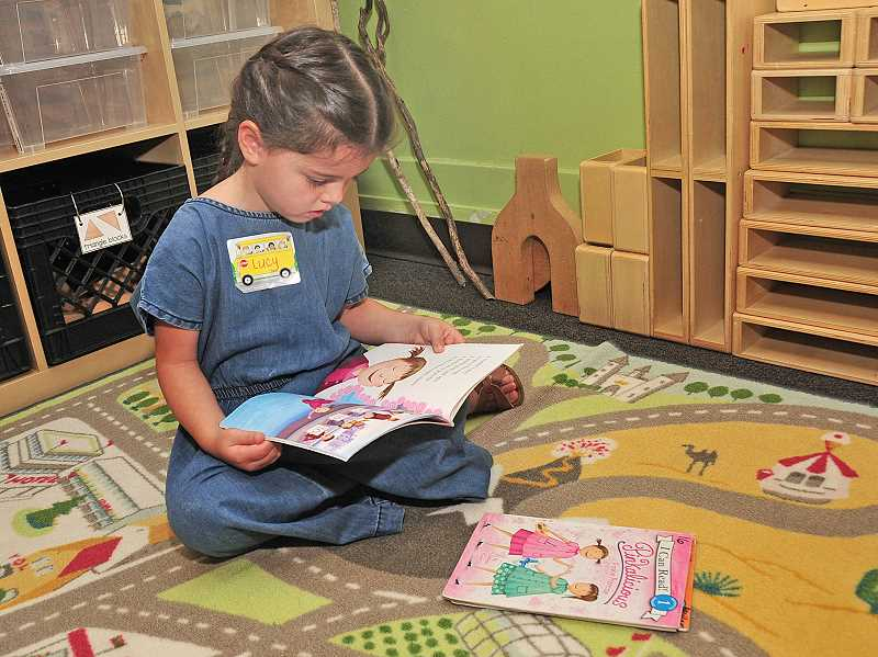 TIDINGS PHOTOS: VERN UYETAKE - Kindergartner Lucy Baumbach finds a quiet spot to read on her first day of school at Willamette Primary Aug. 27.