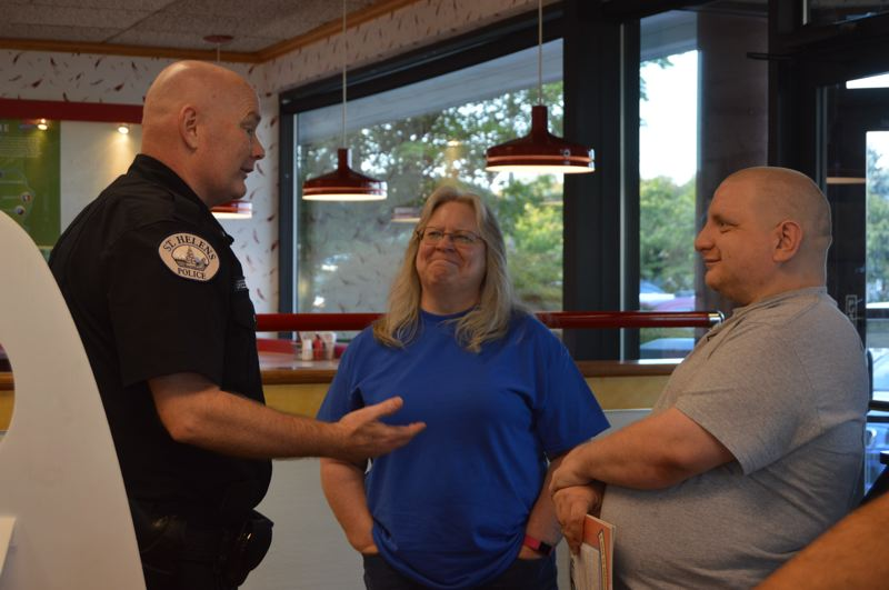 SPOTLIGHT PHOTO: NICOLE THILL-PACHECO - St. Helens Police Chief Brian Greenway, left, chats with Alauna Dodge and Anthony Walz during a Lemonade with the Law event Tuesday, Aug. 29. Walz, who works in St. Helens but lives in Rainier, said his first impression of the new chief is positive, and added he seems like a good guy.