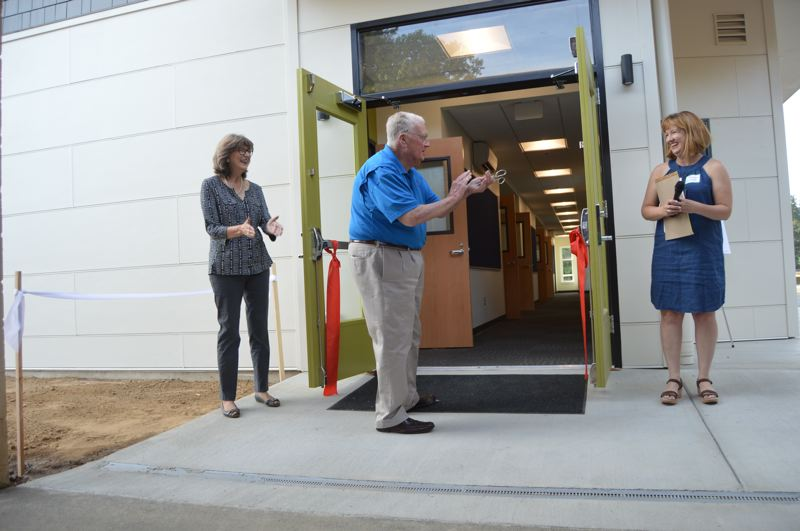 SPOTLIGHT PHOTO: NICOLE THILL-PACHECO - From left to right: Hilarie Miller, George Ray Jr. and Darla Meeuwsen cheer after cutting a ceremonial red ribbon on the doorway of a new middle school wing at Sauvie Island School. The new wing was built after the Joyce Miller Ownens Foundation donated $1.2 million to pay for the building.