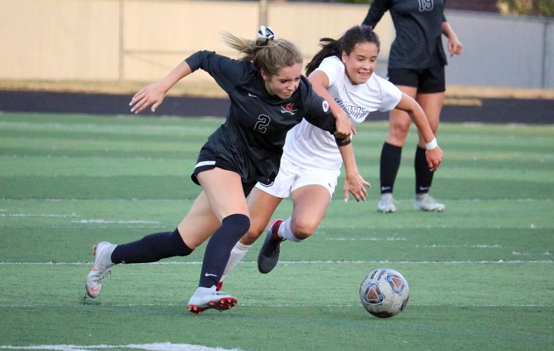 PAMPLIN MEDIA: JIM BESEDA - Clackamas' Emma Anderson (2) battles with Jesuit's Katelyn Duong for possession of the ball during the first half of Wednesday's non-conference girls' soccer game at Clackamas High School.