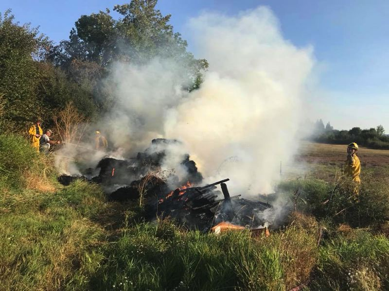 SCAPPOOSE FIRE DISTRICT PHOTO - Firefighters in Scappoose repsond to a hay fire Tuesday, Aug. 28, that ignited on property off Honeyman Road. Throughout the month of August, fire districts imposed bans on all burning due to high fire danger.
