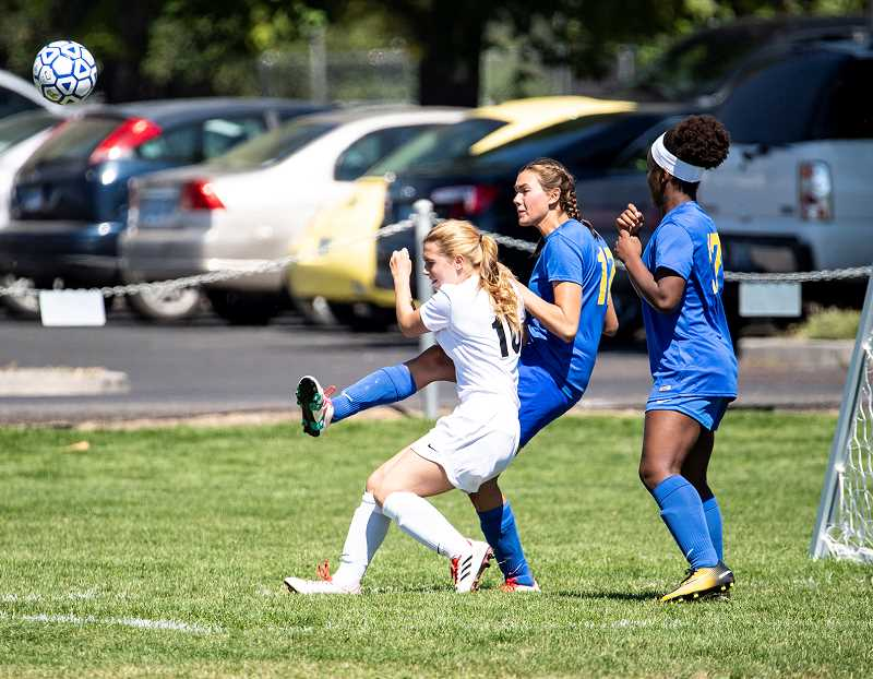 LON AUSTIN/ - Emma Hehn plays a ball away from the Crook County goal following a South Albany corner kick. South Albany's Sarah DeVyldere and Crook County's Zoe Guthrie are also in on the play.