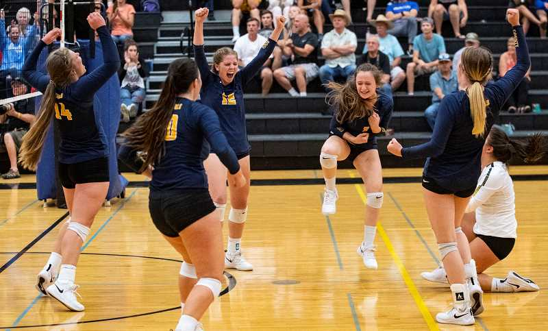 LON AUSTIN/CENTRAL OREGONIAN - The Cowgirl players celebrate after winning the fourth and final set Tuesday night at Sisters. It was the first time in four years that Crook County had been able to defeat Sisters.