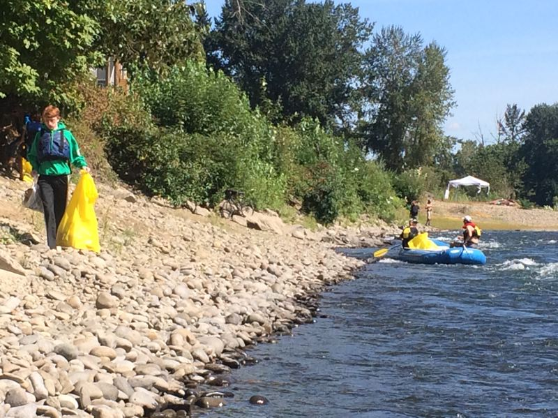 SUBMITTED PHOTO - Volunteers on land and on the water pick up trash during last year's Down the River Clean Up of the Clackamas River.