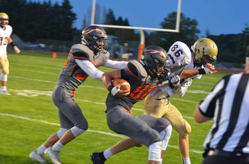 JOHN BREWINGTON - Scappoose's' Gavin Larson fights for yardage following a reception Friday night as the Indians went on to trounce the Astoria Fishermen 27-0 in Scappoose's home opener Aug. 31.