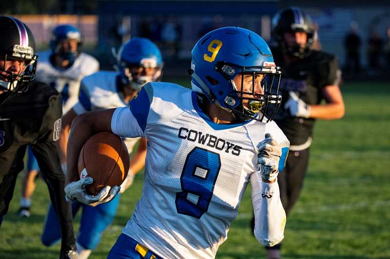 LON AUSTIN/CENTRAL OREGONIAN - Dominic Langley returns a kickoff for a big gain in the Crook County Cowboys 47-25 victory over the Ridgeview Ravens. Langley scored one offensive and one defensive touchdowns in the game.