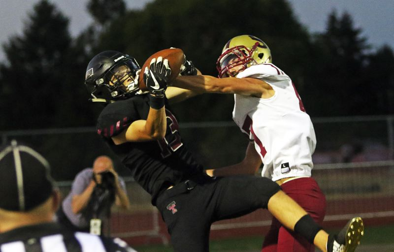 TIMES PHOTO: DAN BROOD - Tualatin senior tight end Jalen Hale (left) wrestles the ball away from Southridge's Joshua Calo for a touchdown catch right before halftime in the Timberwolves' 47-7 win on Friday.