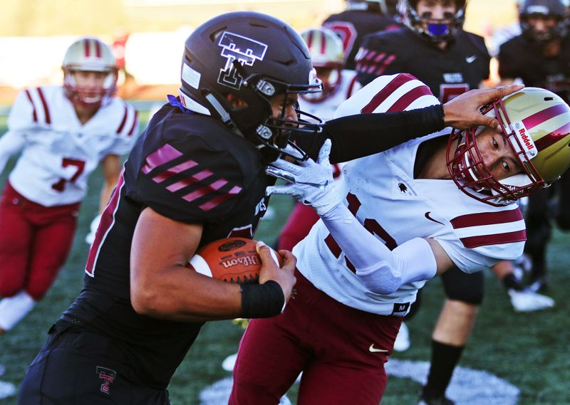 TIMES PHOTO: DAN BROOD - Tualatin junior John Miller (left) pushes away a Southridge defender on the opening kickoff of Friday's season-opening contest.