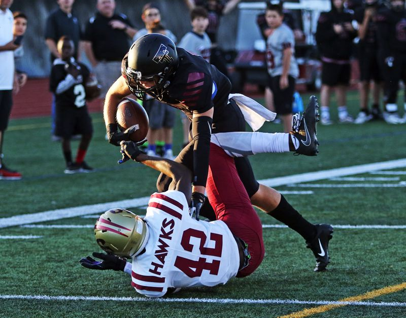 TIMES PHOTO: DAN BROOD - Tualatin junior Luke Marion knocks over Southridge's Keyvaun Eady as he scores the first touchdown of the game in the Wolves' 47-7 win on Friday.