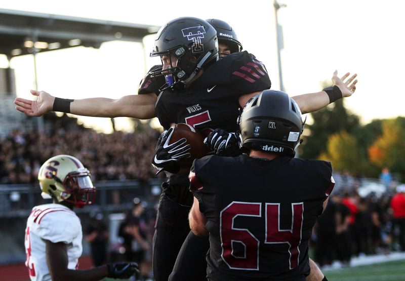 TIMES PHOTO: DAN BROOD - Tualatin senior Kyle Kamp (5) celebrates with senior Quinn McCarthy after scoring on a touchdown run during the Wolves' 47-7 win over Southridge.