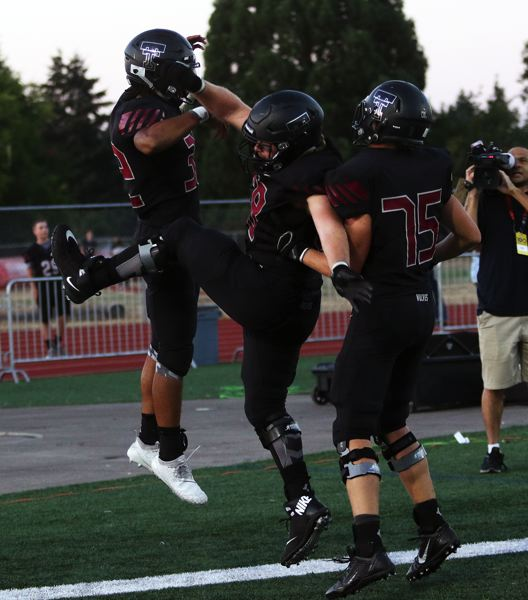 TIMES PHOTO: DAN BROOD - Tualatin's Dominique Loggins (left) celebrates with senior Gavin Moore (center) and junior Brett Gydesen after scoring a touchdown during the Wolves' win over Southridge.