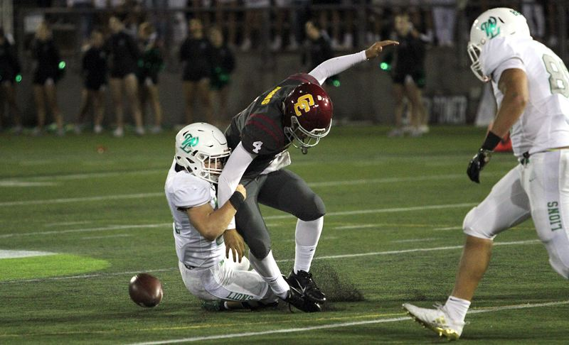 TIDINGS PHOTO: MILES VANCE - West Linn's Max Jacobs sacks Central Catholic quarterback Cade Knighton and forces a fumble during the Lions' 47-41 overtime win at Hillsboro Stadium on Friday.