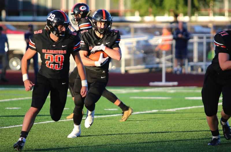 PAMPLIN MEDIA: JIM BESEDA - Gladstone running back Mason Scheehean follows lead blocker Kalehb Newberry during the first quarter of Friday's high school football opener against Banks at Dick Baker Stadium in Gladstone.