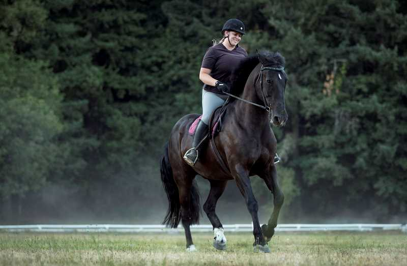 PAMPLIN MEDIA GROUP PHOTO: JAIME VALDEZ - Taryn McAllister, barn director of Lake Oswego Hunt, rides Zeus, a former member of the Portland Police Bureau's Mounted Patrol Unit, on the Hunt property. McAllister adopted Zeus when the unit disbanded in 2017.