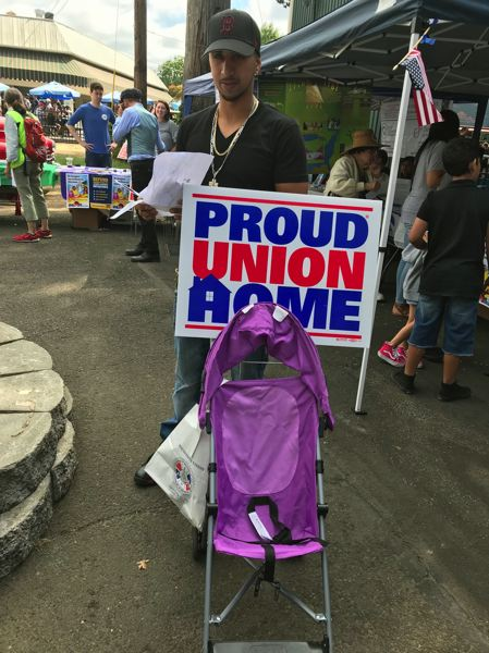 TIMES PHOTO: DANA HAYNES - Ramiro Losoya of Salem turns his family's baby stroller into a union billboard.