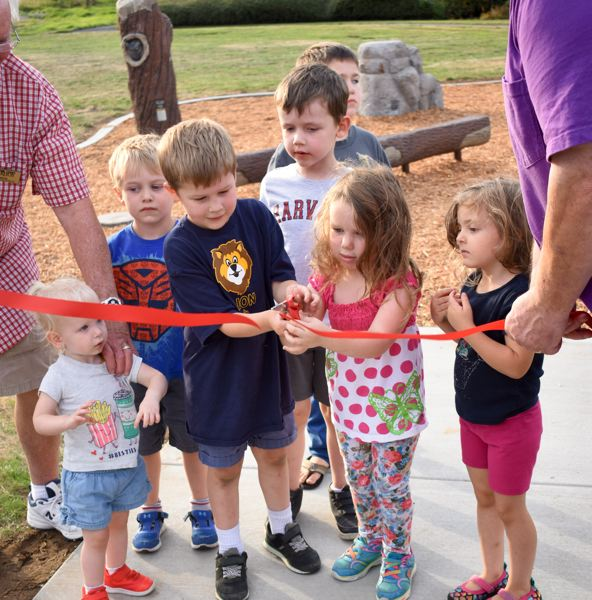 OUTLOOK PHOTO: MATT DEBOW  - Matilda Williams, 3, and her older brother Atticus, 5, cut the ribbon at Lakeshore Park in Fairview on Wednesday, Aug. 29.