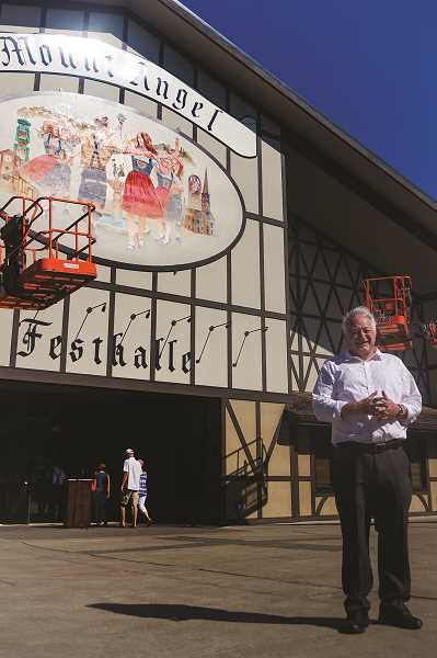 PATRICK EVANS - Silverton painter David McDonald stands in front of his mural, newly mounted on the Mount Angel Festhalle.