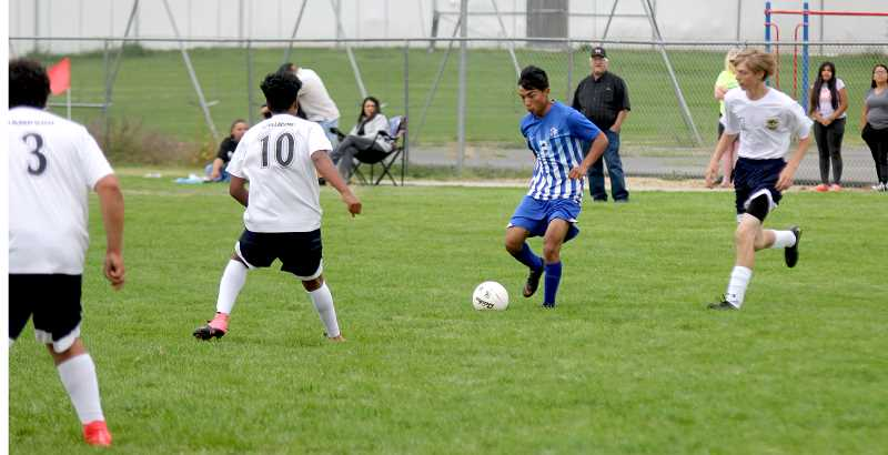 STEELE HAUGEN - Alex Diaz blows past two Crook County defenders in the team's 9-1 win Aug. 31. Diaz ended the game with two goals and two assists.