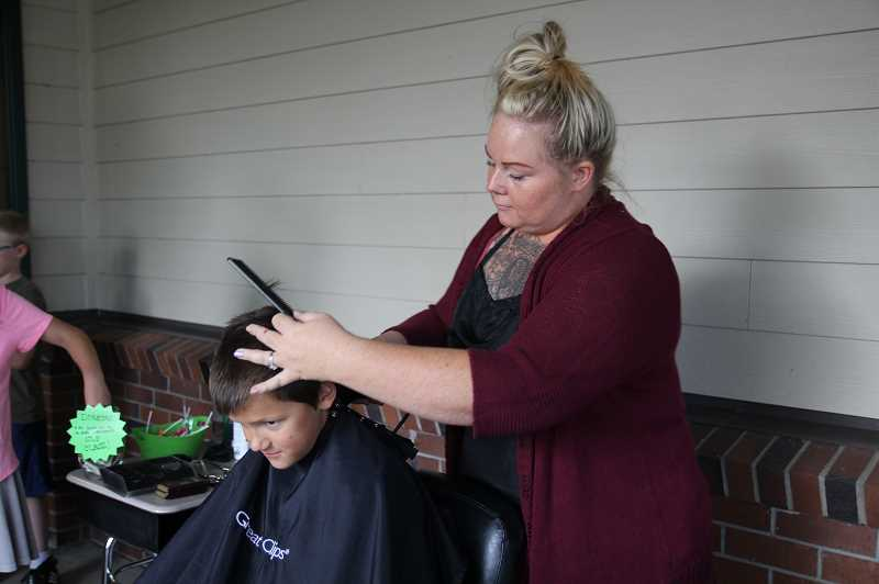 LINDSAY KEEFER - Crystal Diamond-Lee (right) gave free haircuts to incoming students, including second-grader Beckett Krueger.