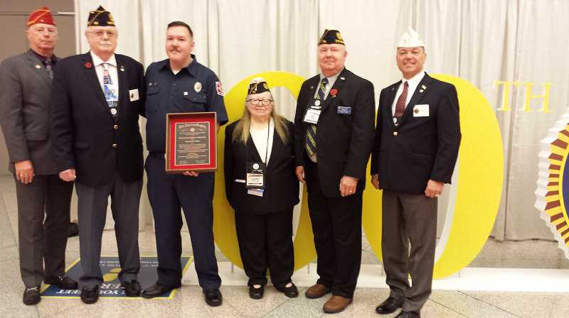 CONTRIBUTED PHOTO: FLYNN PHILIPS - Estacada volunteer firefighter Damon Faust (center) is pictured with members of the American Legion after receiving the organizations national firefighter of the year award.