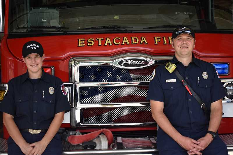 ESTACADA NEWS PHOTO: EMILY LINDSTRAND - Estacada firefighters Brooke Gramer and Chris James smile in front of one of the departments rigs.'